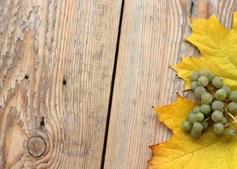 Marple leaves and grapes on wooden texture