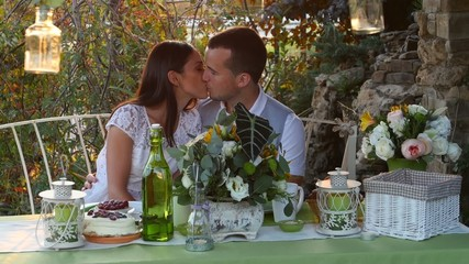 Man and woman kissing at the holiday table