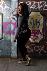 Happy Black Woman Posing at Wall with Vandals
