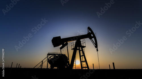 Operating oil and gas well profiled on sunset sky - 71506299