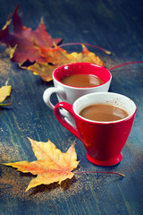 Two cups of coffee with autumn leaves, on wooden background