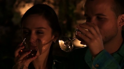 Young couple in love drinking wine and kissing by candlelight