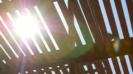 The sun shines through a fence