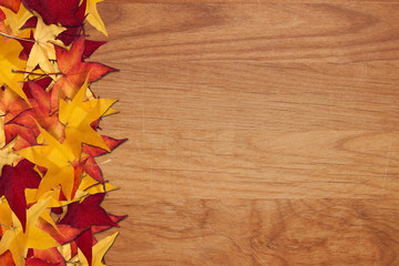 Fall leaves on wood grain background