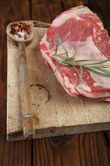 raw shoulder lamb on wooden board and table