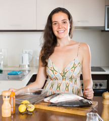 Woman cooking fish at kitchen