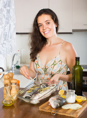 Woman cooking fish at home kitchen