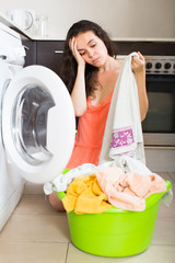 Tired woman near washing machine