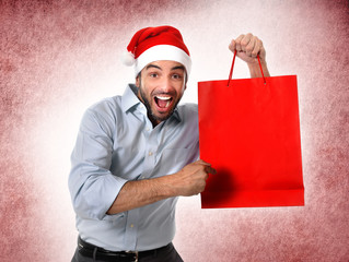 man in santa hat holding Christmas shopping bag smiling happy