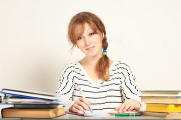 Charming  girl sitting at table with books studying