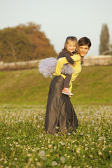 Happy Family Mother And Daughter On Daisy and Dandelion Field