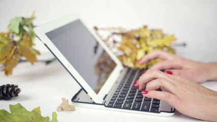 Close up on woman's hands typing on her laptop in bright studio