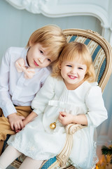 Two evening dressed children are sitting on a chair