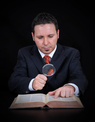 Businessman is using the magnifying glass