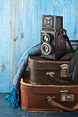 Retro camera and old suitcases on a blue wooden background.