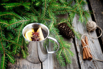 Mulled wine in the mug on the background of fir branches