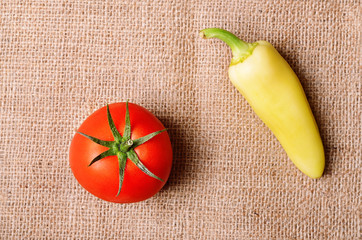 Tomato and pepper on sackcloth background