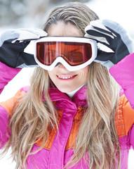 Frau im Winter setzt Skibrille auf