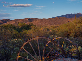 Rusted carriage weels in Arizona desert at sunset