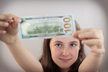 Beautiful teen girl holding US dollars