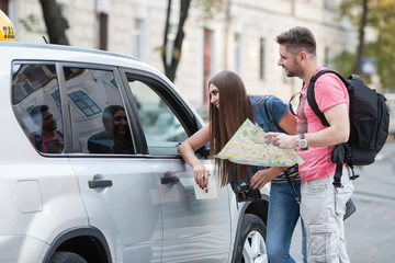 tourists ask for directions from a taxi driver