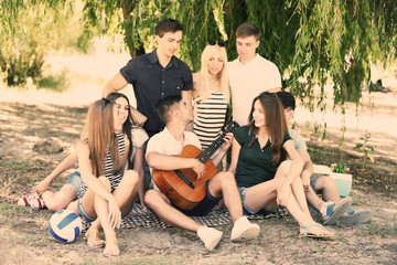 Beautiful young people with guitar having fun in park