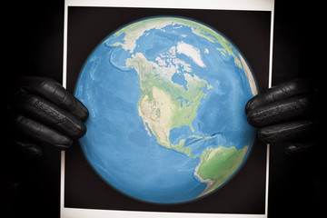 Person holding a photo of the Earth