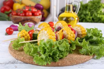 Sliced vegetables on picks on board on table close-up