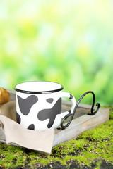 Mug of tasty milk on nature background
