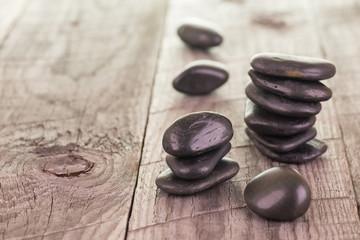 Balanced black stones on weathered deck background