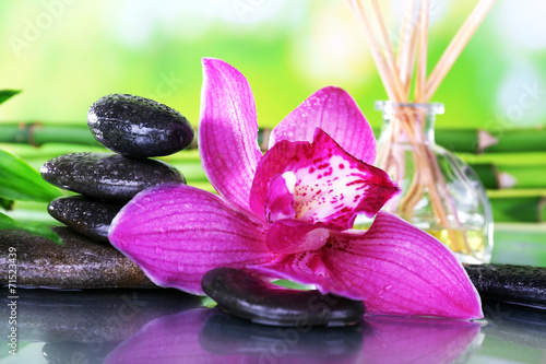 Foto op Canvas Lilac Spa stones, sticks, bamboo branches and lilac orchid