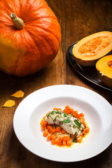 Studio closeup of seared scallops, garnished pumpkin.  Fish with