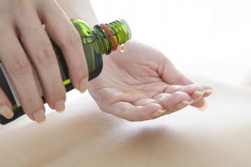 Esthetician put the massage oil on hand