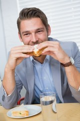 Smiling businessman eating a sandwich