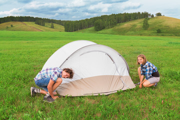 Teenage boy and girl arranges tourist tent
