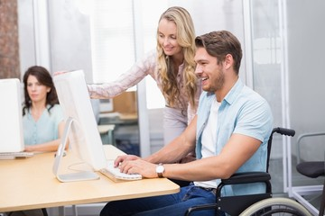 Casual businesswoman helping colleague in wheelchair