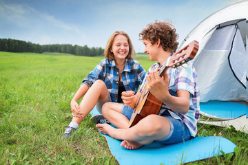 Teenage boy and girl near the tent play guitar