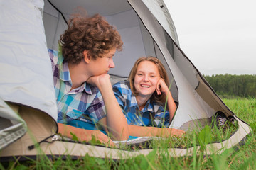 Teenage boy and girl near a white tent