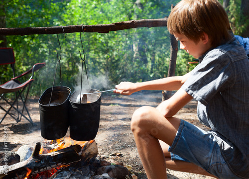 Tuinposter Kamperen Child cooking on campfire