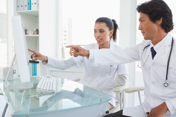 Two doctors pointing to computer screen