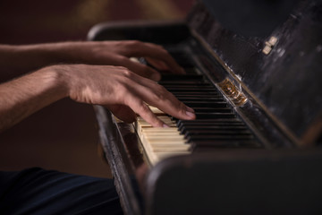 Close-up picture of hands of a musician playing on the black anc