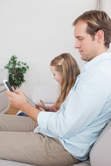 Casual father and daughter using tablet