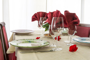 Setting table in a restaurant with red decorations