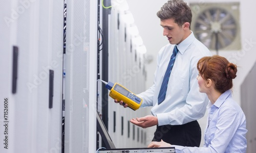 canvas print picture Team of technicians using digital cable analyser on servers