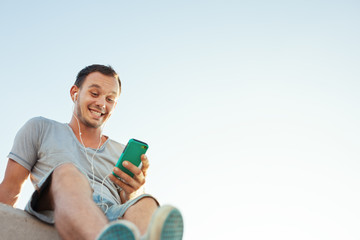 handsome man with mobile smartphone sitting on the bench