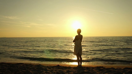 Silhouette of a girl on a beach during the sunset