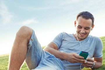 handsome man with mobile smartphone sitting in the park