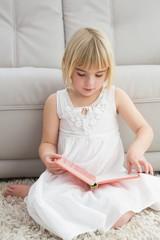 Little girl sitting on the floor reading storybook