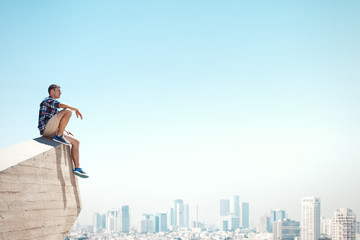 Young man sitting on a cliff and looking at the city