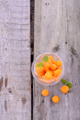 organic fresh northern cloudberries on a wooden background